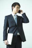 電話をするスーツ姿の20代男性