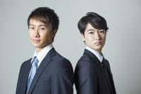 背中を合わせるスーツ姿の20代男性2人 10161018739| 写真素材・ストックフォト・画像・イラスト素材|アマナイメージズ