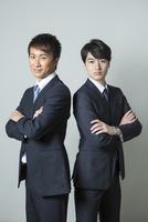 腕組みをするスーツ姿の20代男性2人