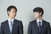 お互いを見つめるスーツ姿の20代男性2人