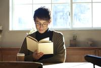 部屋で読書をする20代男性 10161018791| 写真素材・ストックフォト・画像・イラスト素材|アマナイメージズ