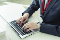 パソコンを使い仕事をするスーツ姿の20代男性手元