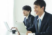 オフィスで仕事をする笑顔の20代男性2人 10161018859| 写真素材・ストックフォト・画像・イラスト素材|アマナイメージズ