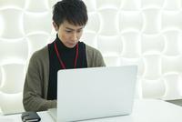 パソコンに向かい仕事をする21代男性