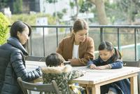 テラス席に座る親子2組 10161019051| 写真素材・ストックフォト・画像・イラスト素材|アマナイメージズ