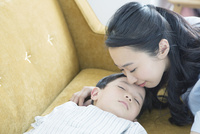 寝ている子供とおでこにキスをする母親