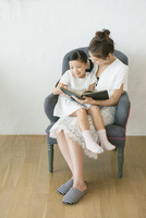 ソファに座り本を読む笑顔の親子 10161019120| 写真素材・ストックフォト・画像・イラスト素材|アマナイメージズ