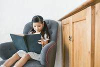 ソファに座り本を読む女の子