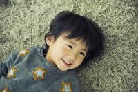 ラグに寝そべる笑顔の男の子