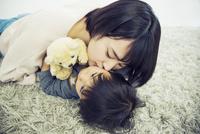 寝転がりこどもにキスをする母親 10161019179| 写真素材・ストックフォト・画像・イラスト素材|アマナイメージズ
