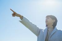 青空の下指差しをする20代女性 10161019193  写真素材・ストックフォト・画像・イラスト素材 アマナイメージズ