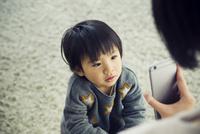スマホを見せらせる男の子 10161019260| 写真素材・ストックフォト・画像・イラスト素材|アマナイメージズ