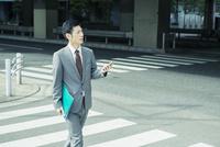 スマホを手に持ち歩くスーツ姿の30代男性