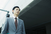 屋外に立つスーツ姿の30代男性 10161019311| 写真素材・ストックフォト・画像・イラスト素材|アマナイメージズ