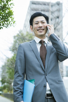 屋外で電話をするスーツ姿の30代男性