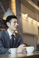 カフェで打ち合わせをするスーツ姿の30代男性