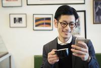カフェでスマホを見る30代男性