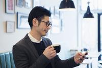 カフェでスマホを見る30代男性 10161019332| 写真素材・ストックフォト・画像・イラスト素材|アマナイメージズ