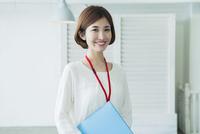 ファイルを持つ笑顔の20代女性 10161019424| 写真素材・ストックフォト・画像・イラスト素材|アマナイメージズ