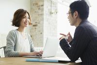 男性と会話をする仕事中の20代女性 10161019436| 写真素材・ストックフォト・画像・イラスト素材|アマナイメージズ