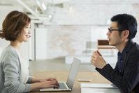 男性と会話をする仕事中の20代女性 10161019440| 写真素材・ストックフォト・画像・イラスト素材|アマナイメージズ