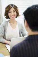 男性と会話をする仕事中の20代女性 10161019446| 写真素材・ストックフォト・画像・イラスト素材|アマナイメージズ