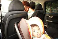 ベビーチェアに座る赤ちゃんを見つめる母親