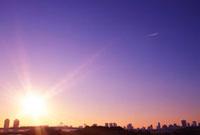 夕日のお台場を走るゆりかもめと飛行機雲