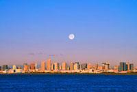 満月と朝日に輝く東京都心のビル群