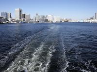 観光船の白い航跡とウォーターフロントのビル群