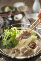 博多風水炊きの鶏肉を食べる