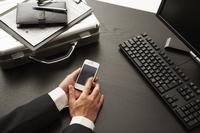 机でスマートフォンを触るビジネスマンの手
