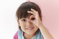 ピンク色の壁と目元で手で丸を作りカメラを覗き込む女の子