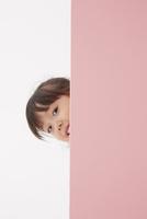 ピンク色の壁から顔を出す女の子