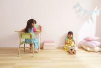 ピンク色の壁の子供部屋で勉強机に座っている女の子と床に座っている女の子の姉妹