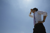 青空の下で額の汗を拭うビジネスマン