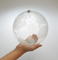 透明な地球儀を持つ女性の手