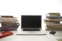 白い机のノートパソコンと本と資料