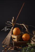 木箱に置かれた二個のハロウィンカボチャとほうきと鷹のオブジェ