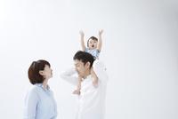 両手を上げている赤ちゃんを肩車しているお父さんとお母さん