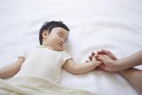 寝ている赤ちゃんと手をつないでいるお母さんとお父さんの手