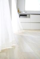風になびくカーテン横のキッチン