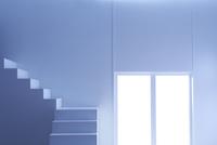 窓から光の入る明るく白い部屋と階段