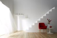 光の入る明るく白い部屋にある白い階段と風でなびくレースカーテン