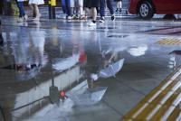 雨で駅の歩道に写りこむ人の流れ