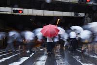 歩道で傘を持ってたたずむ女性