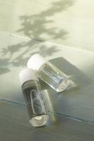 青い天板の上の透明なボトルと木漏れ日