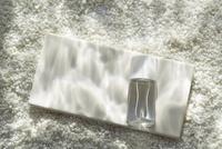 白い砂利に波紋が映った水中イメージとタイルと小瓶