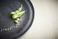 黒の皿の上の枝豆と塩