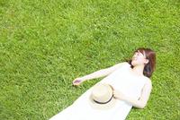 草原に寝転ぶ若い女性 10179008619| 写真素材・ストックフォト・画像・イラスト素材|アマナイメージズ